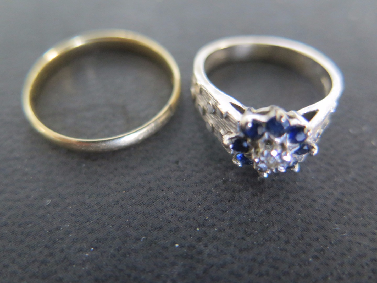 An 18ct yellow gold wedding band size O and an 18ct white gold cluster ring...