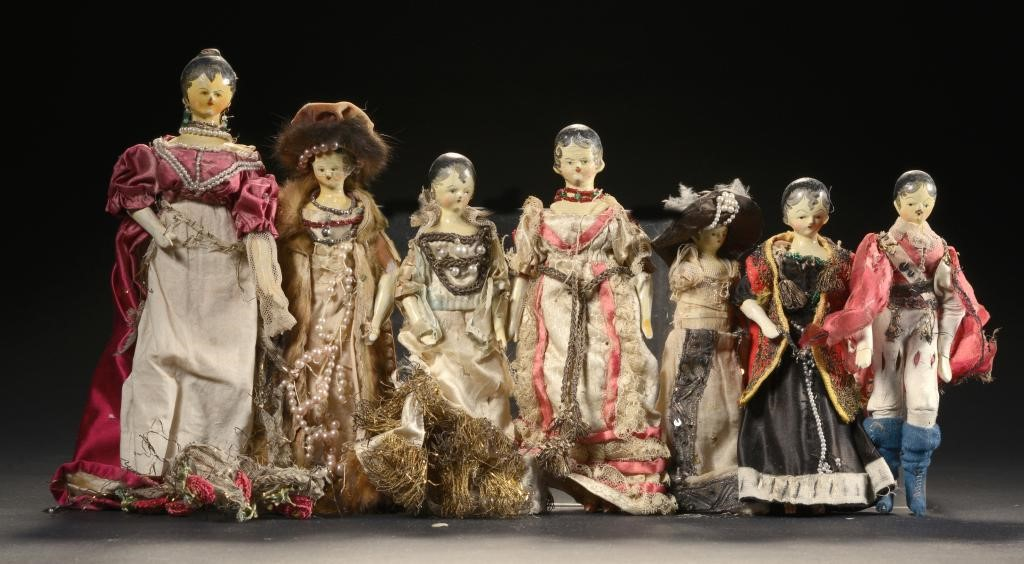 SEVEN SIMILAR PAINTED WOODEN PEG DOLLS IN CONTEMPORARY DRESS Image